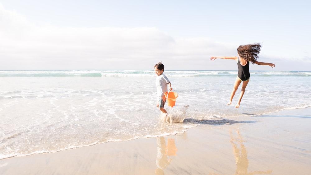 2 boys running on beach during daytime