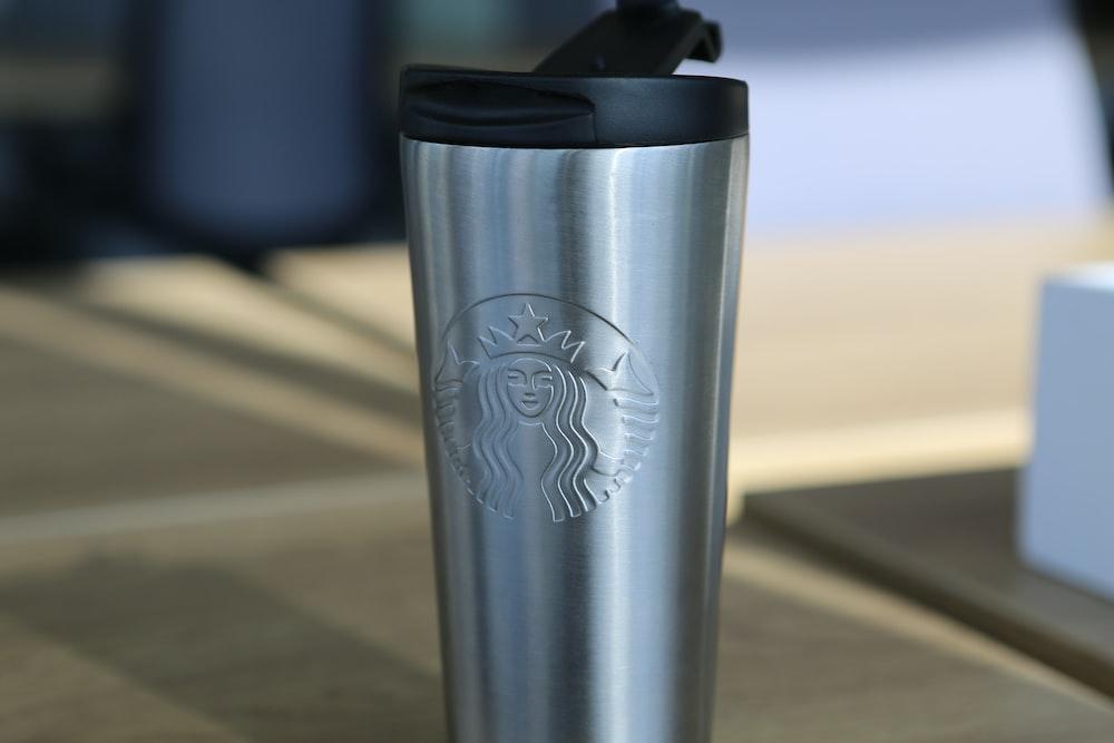 silver starbucks travel mug on brown wooden table