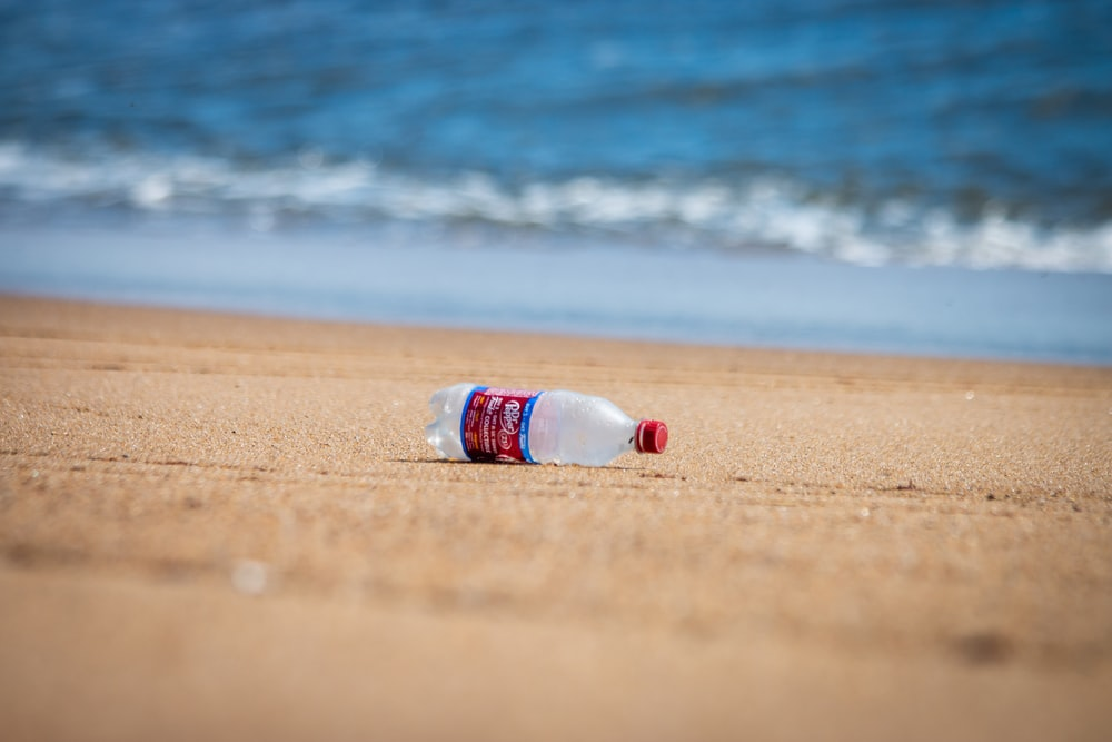 white and blue plastic bottle on beach shore during daytime