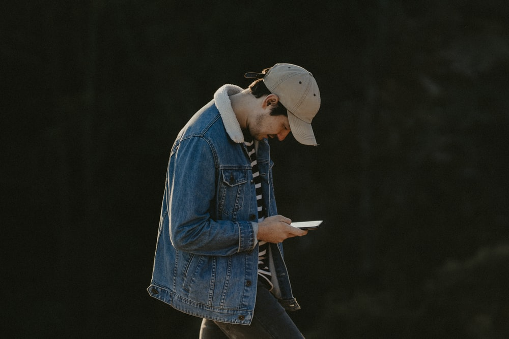 woman in blue denim jacket and brown hat holding white book