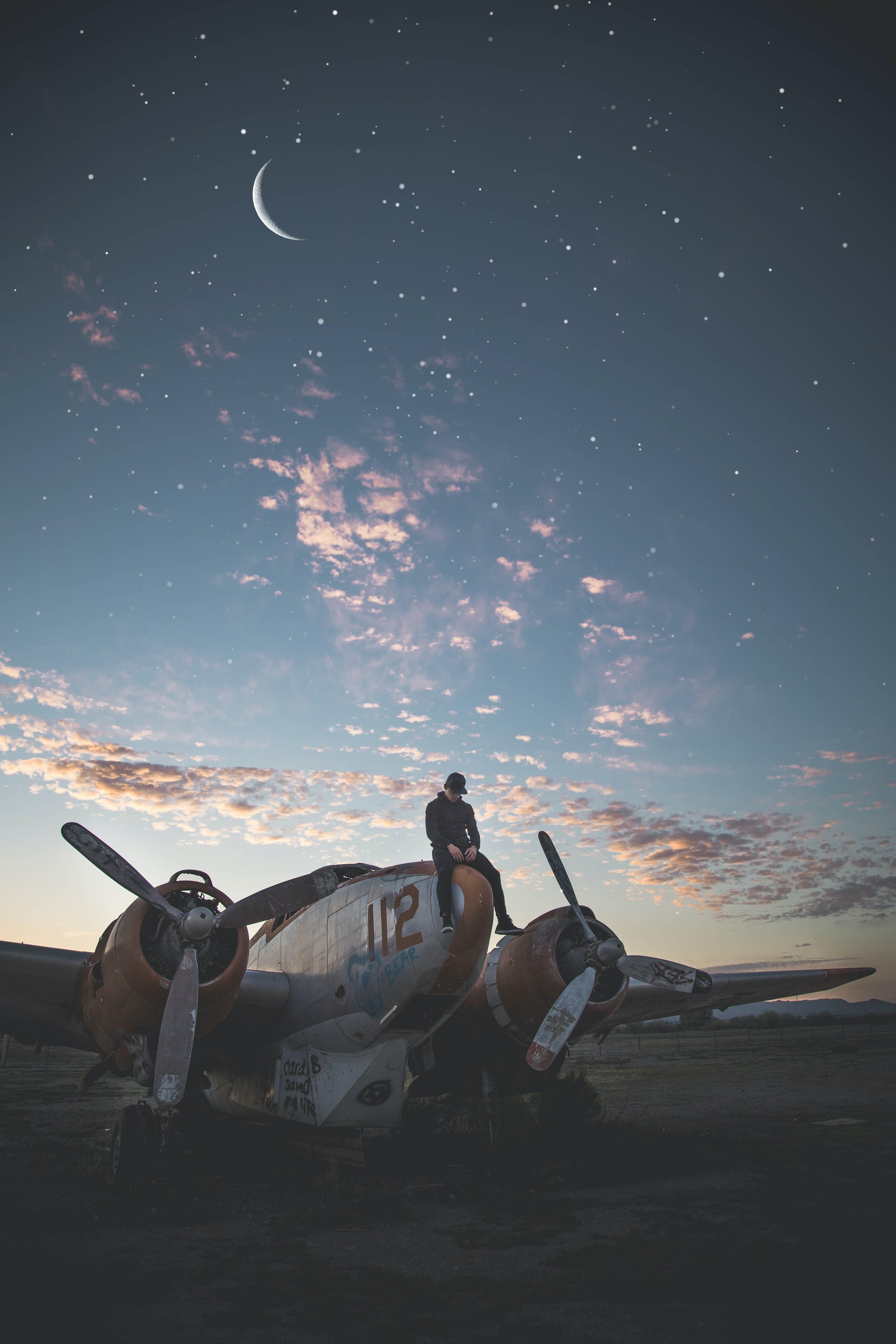 Model sitting on a scrap airplane with starry sky
