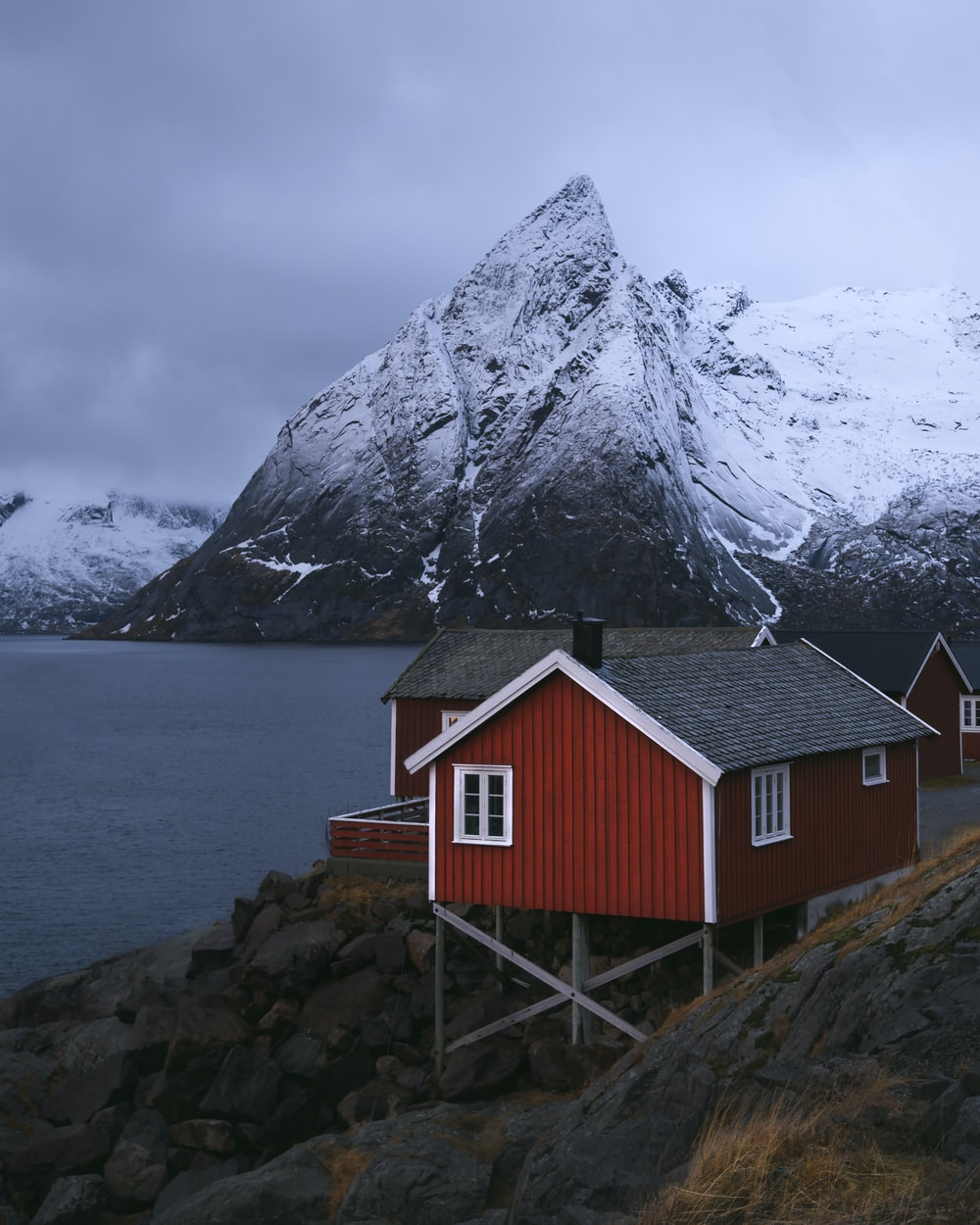 red and white wooden house near body of water and snow covered mountain during daytime