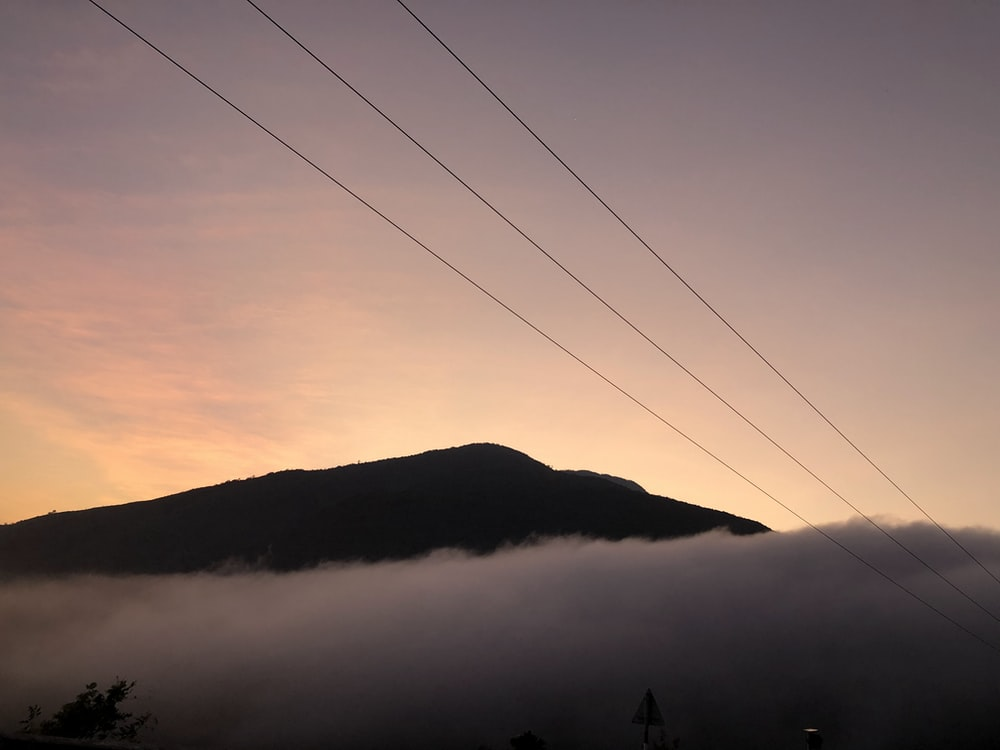 silhouette of mountain under cloudy sky during daytime