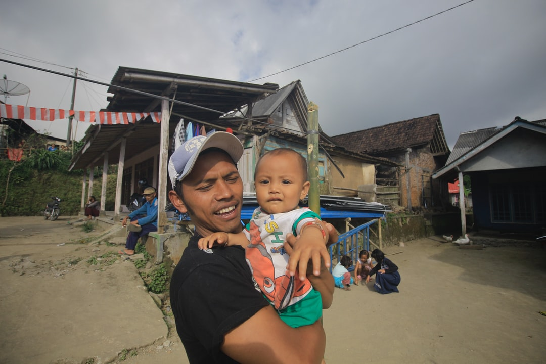 Man with child with a background of house in slums.