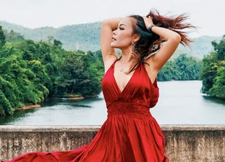 woman in red sleeveless dress standing near body of water during daytime