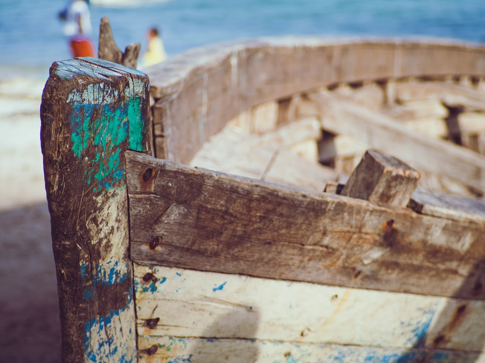 brown wooden boat on sea shore during daytime