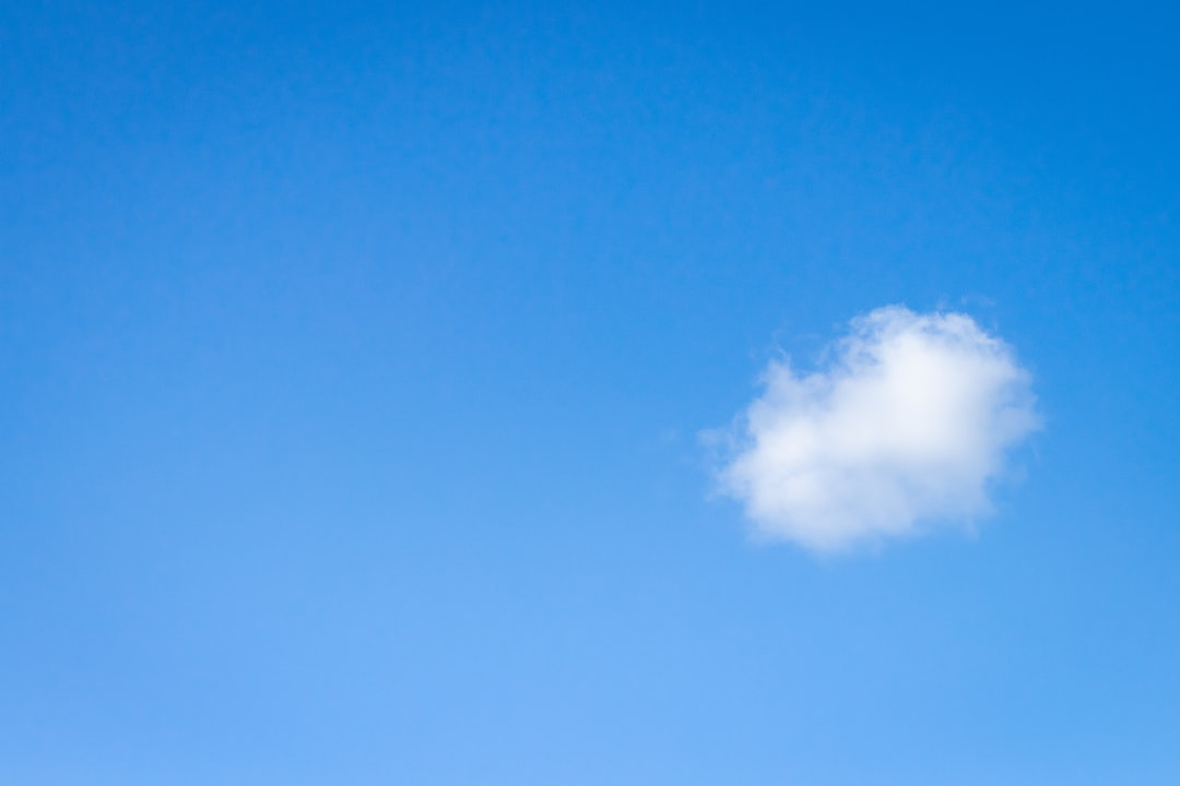 small single fluffy white cloud floating in the blue sky