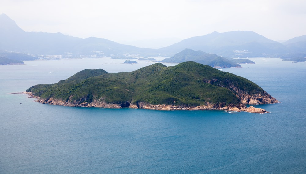 green mountains beside blue sea during daytime