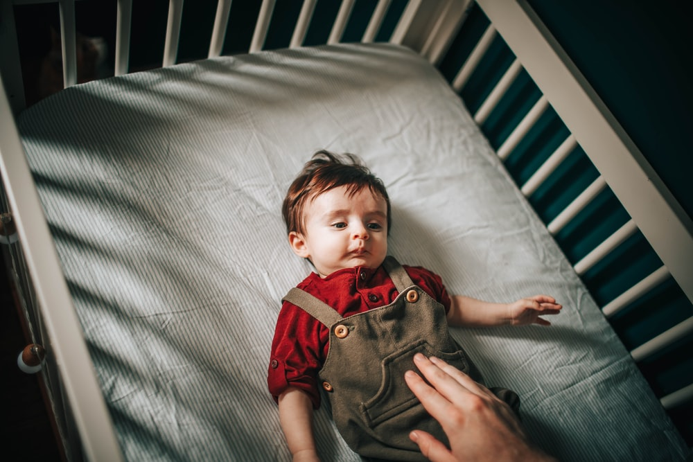 baby in red and gray button up shirt lying on white bed