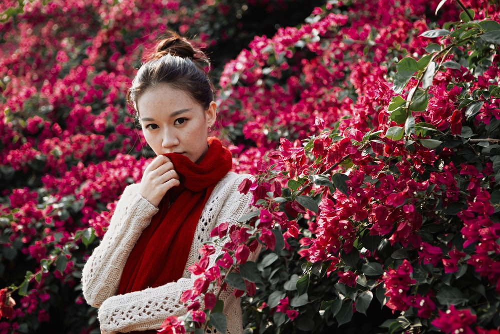 girl in red scarf standing beside red flowers during daytime