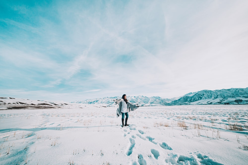 woman in white jacket walking on snow covered field during daytime