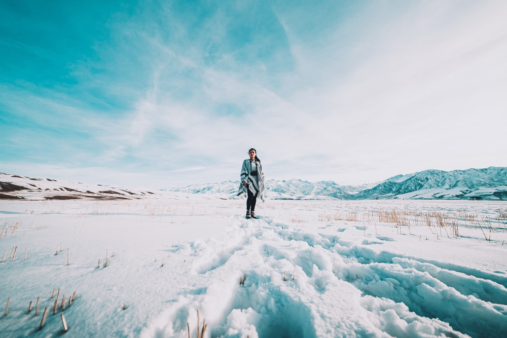 woman in black jacket walking on snow covered ground during daytime