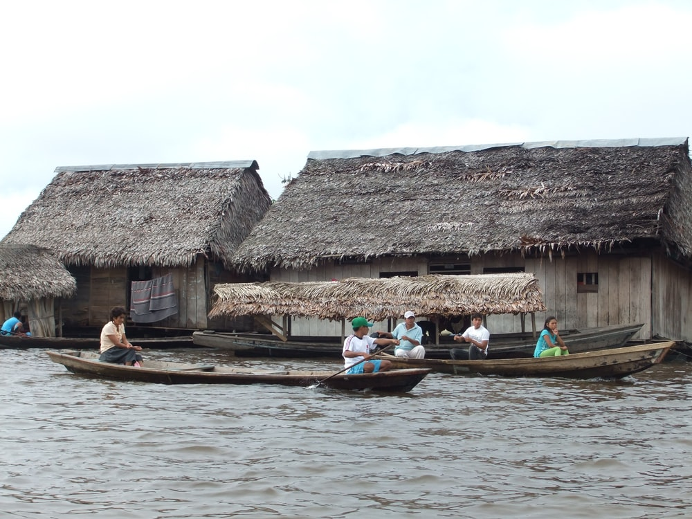 people riding on boat near brown wooden house during daytime