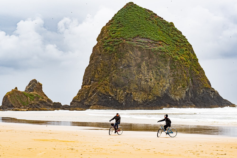 people riding bicycle on beach during daytime