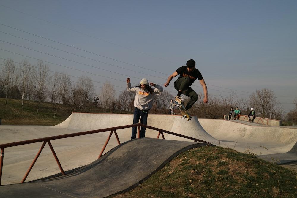 man in black t-shirt and black pants doing skateboard trick