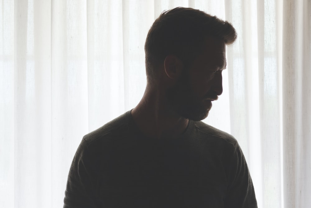 man in gray crew neck shirt standing near white window curtain