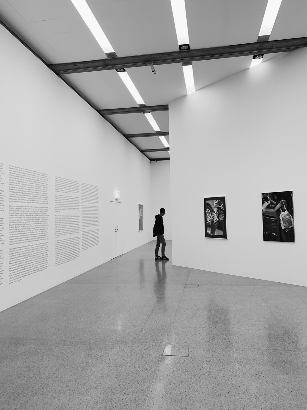 woman walking on hallway in grayscale photography