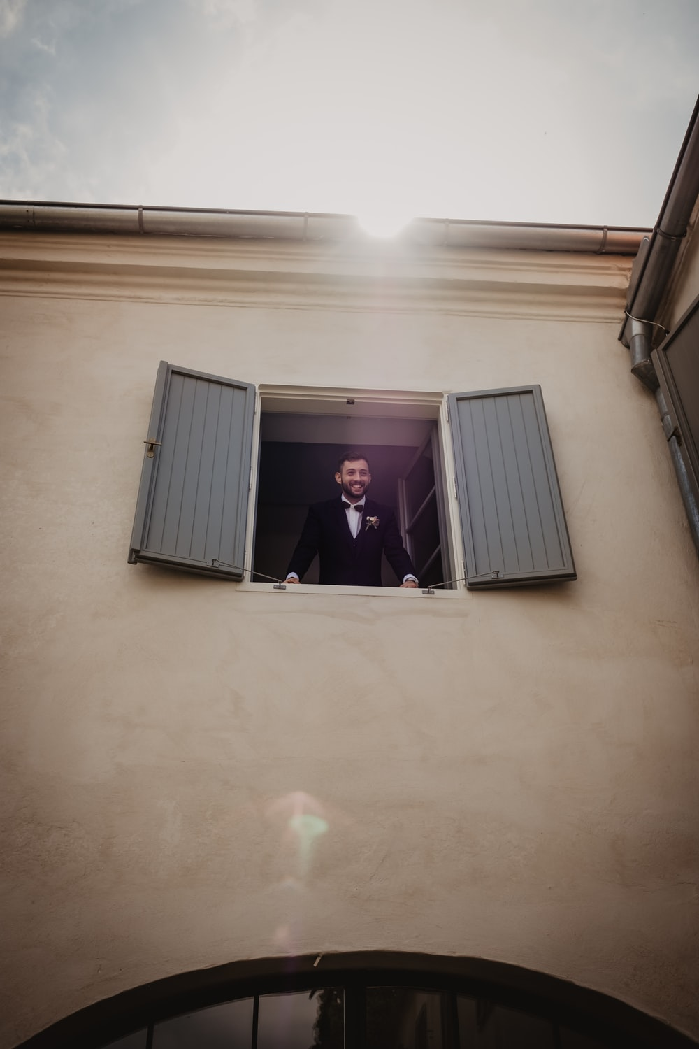 man in black suit jacket standing near white window blinds