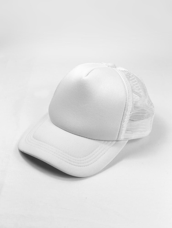 white baseball cap on white surface