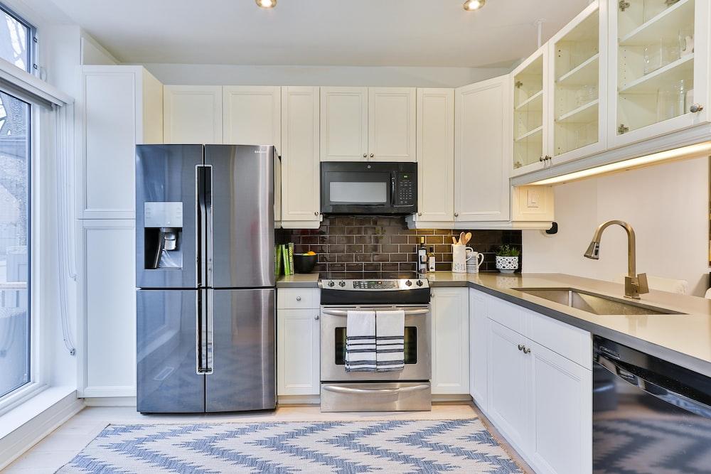 silver french door refrigerator beside white wooden kitchen cabinet