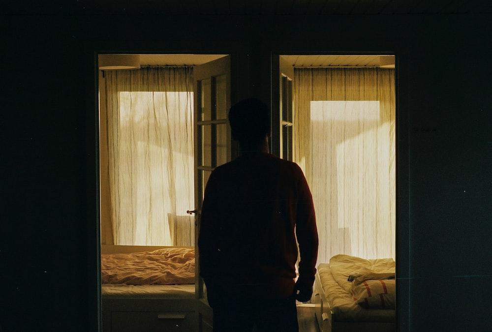 man in red long sleeve shirt standing near window