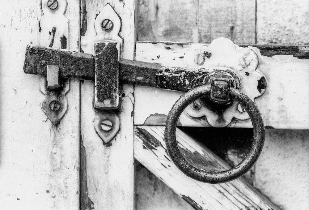 grayscale photo of metal chain on wooden door