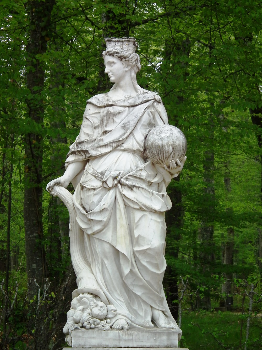 angel statue near green trees during daytime