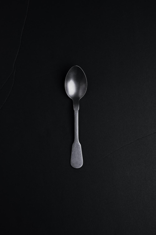 silver spoon on black textile