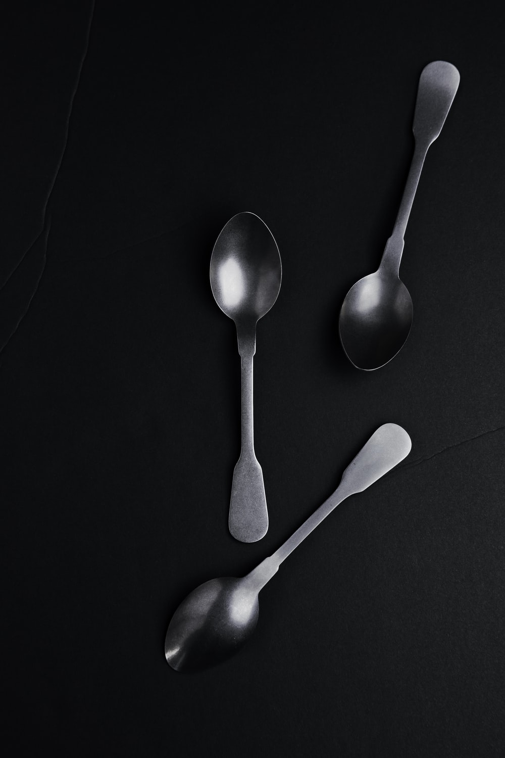 silver spoon on black surface