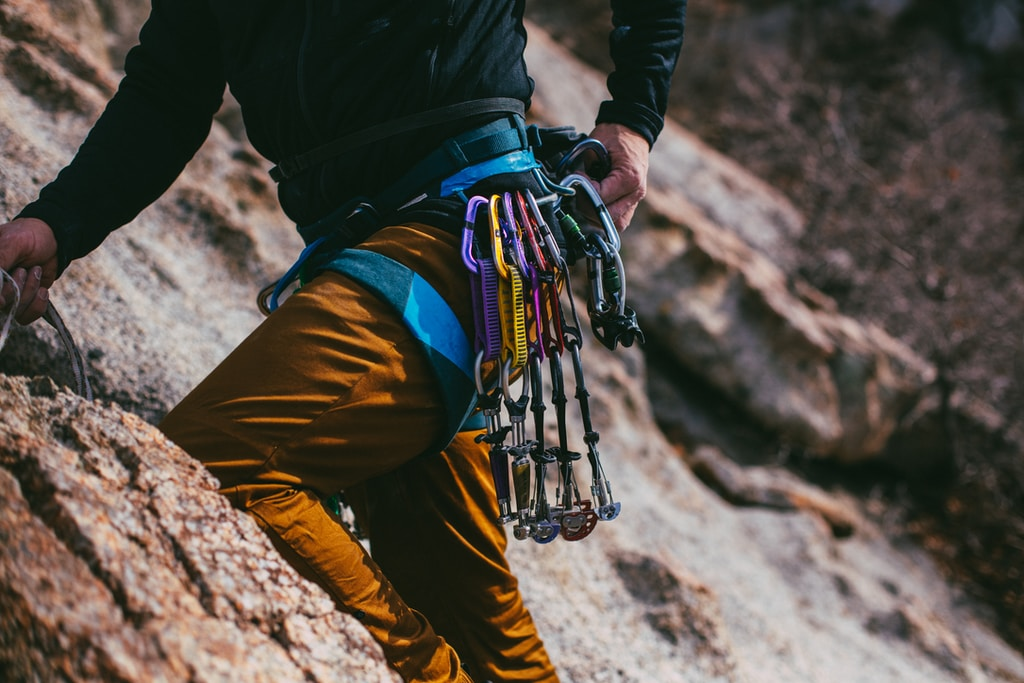 person in black jacket and brown pants with hiking backpack climbing mountain during daytime
