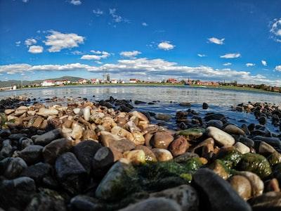 Mitrovicë brown rocks on seashore under blue sky during daytime