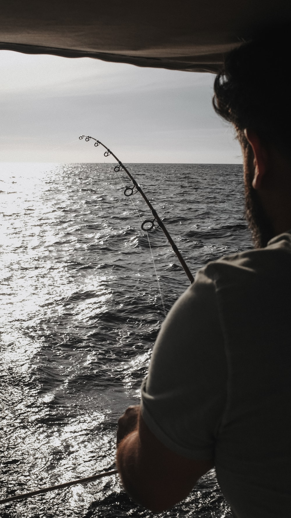 person in black jacket fishing during daytime