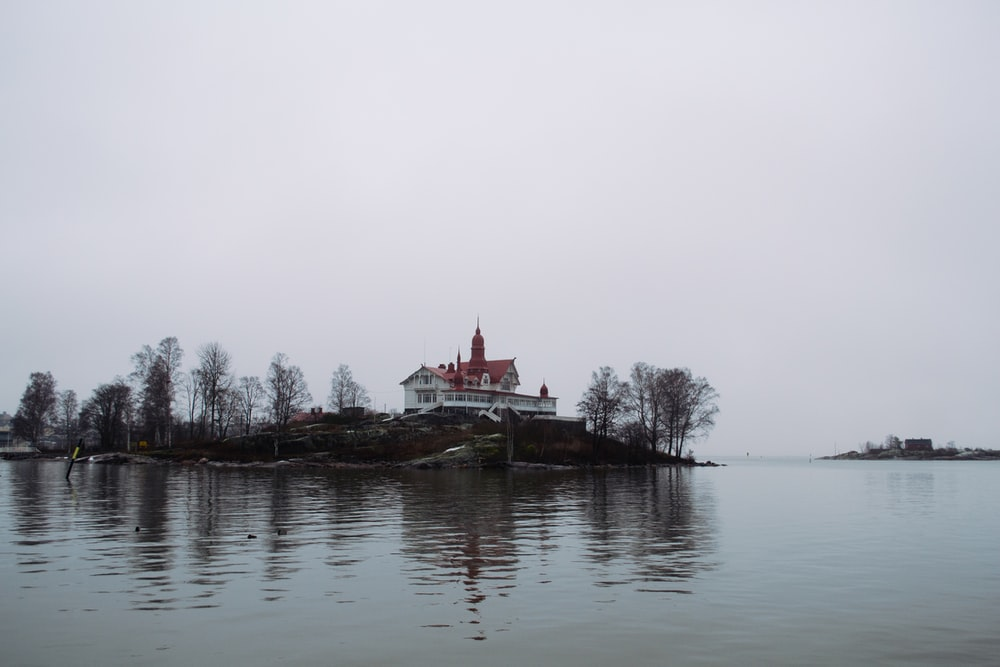 white and red house near body of water during daytime