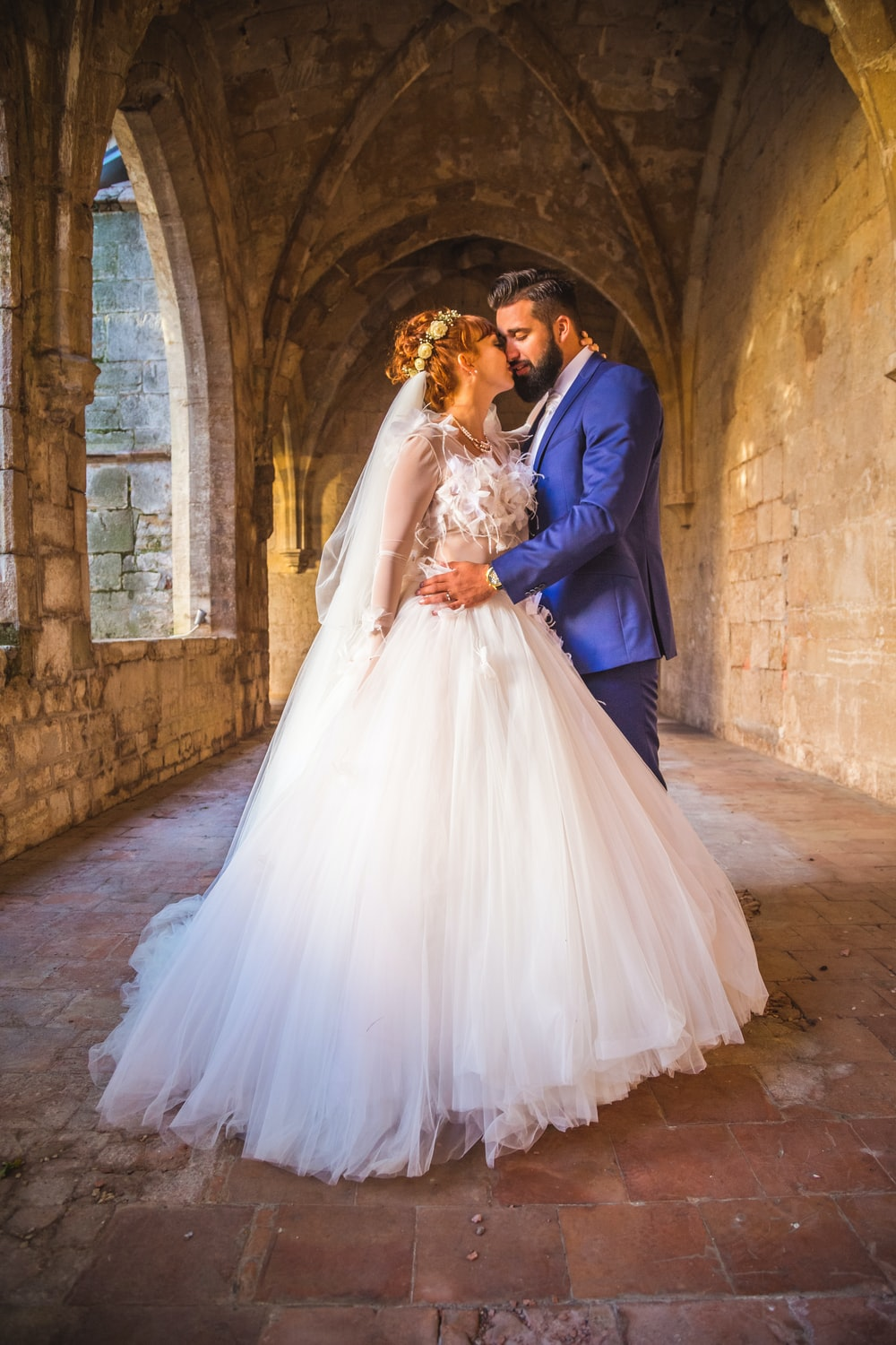man in blue suit and woman in white wedding dress