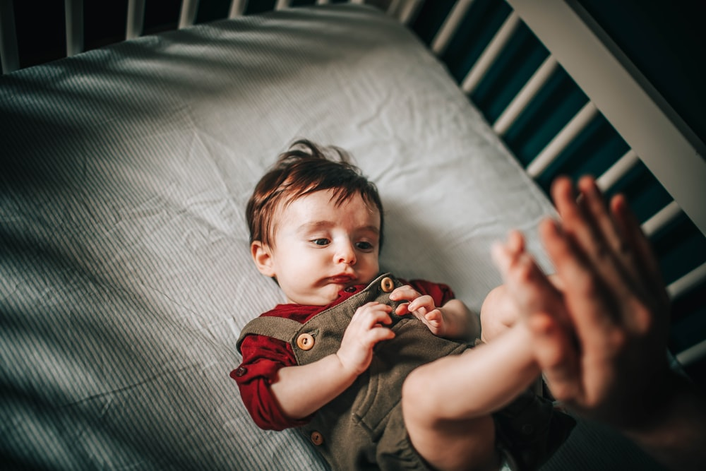 baby in gray shirt lying on bed