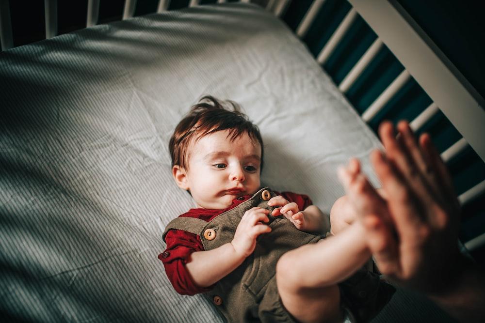 Kleinkind mit gelangweiltem Gesichtsausdruck in einem Laufstall