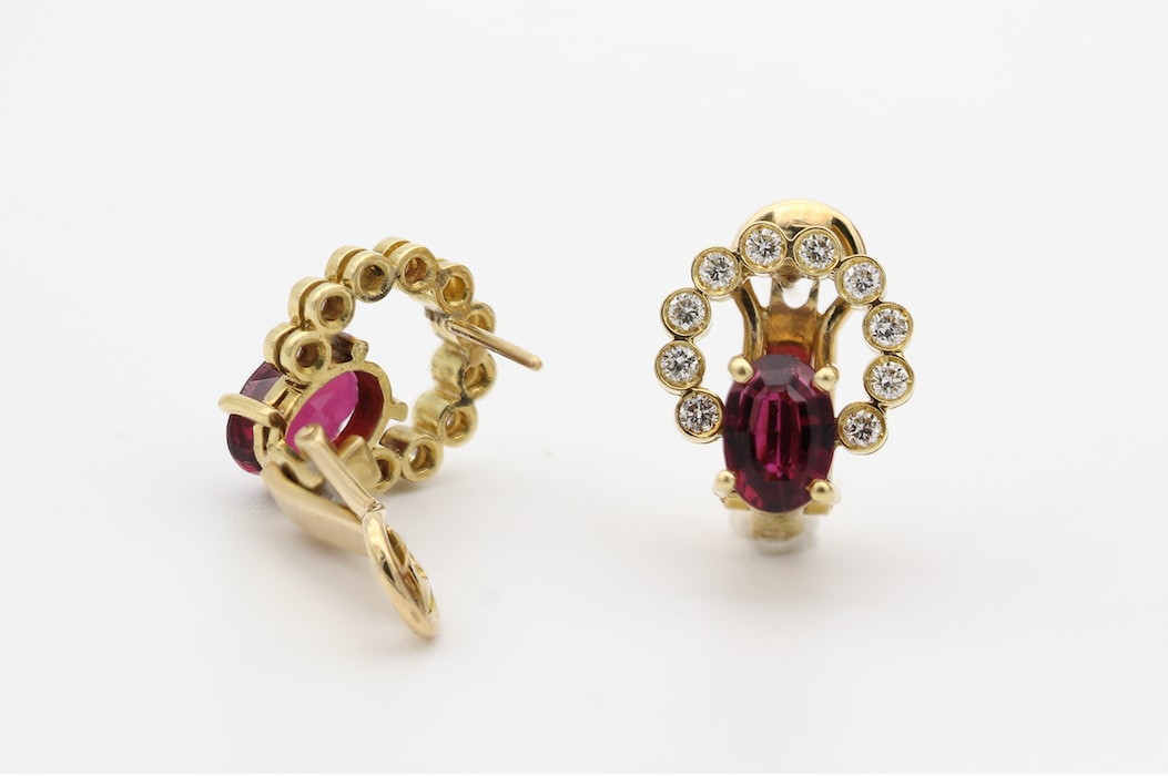 Gold diamond encrusted earings with ruby stones against white background for jewelry repair concept