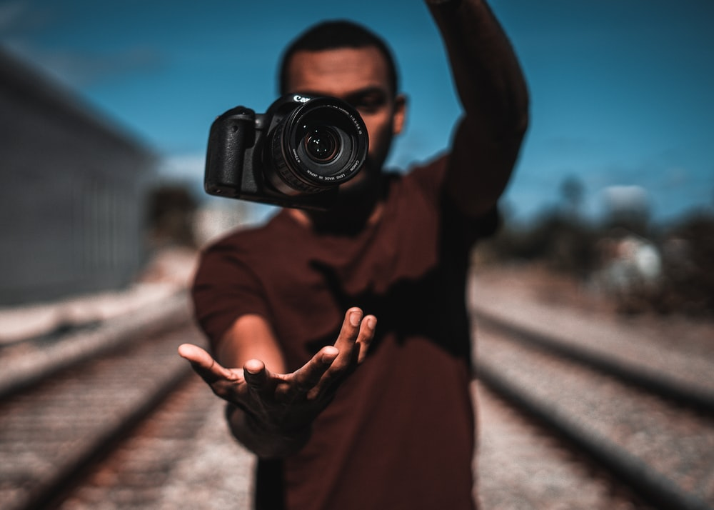 person in brown long sleeve shirt holding black dslr camera