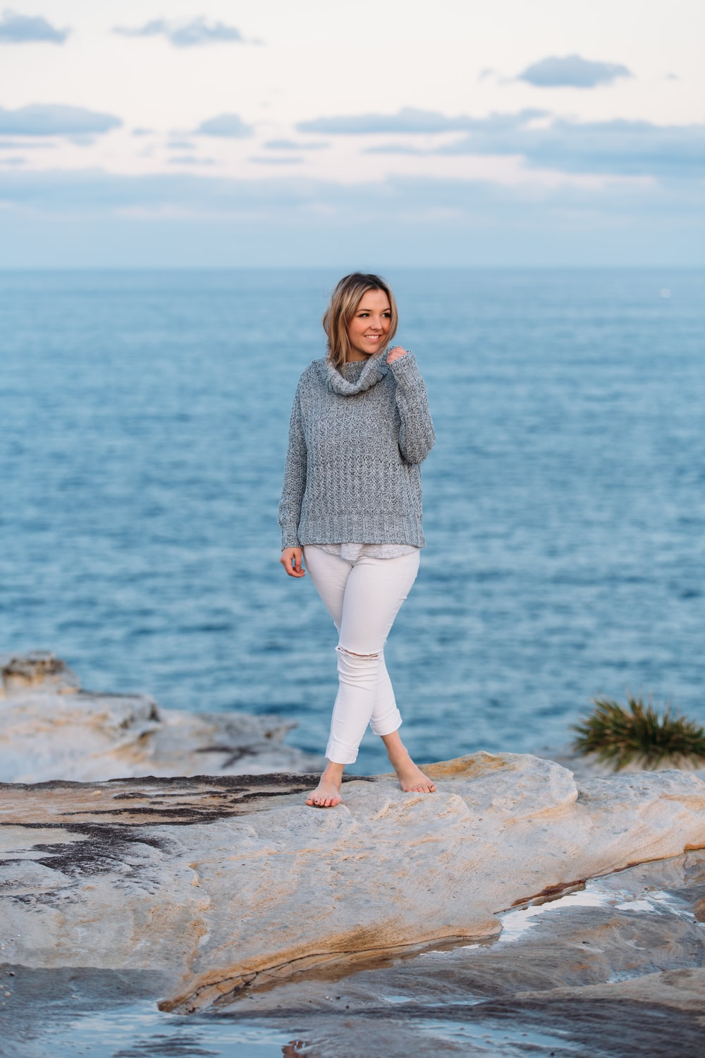 woman in gray sweater and white pants standing on brown rock near body of water during