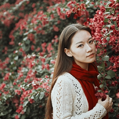 woman in white knit sweater and red scarf standing beside red flowers