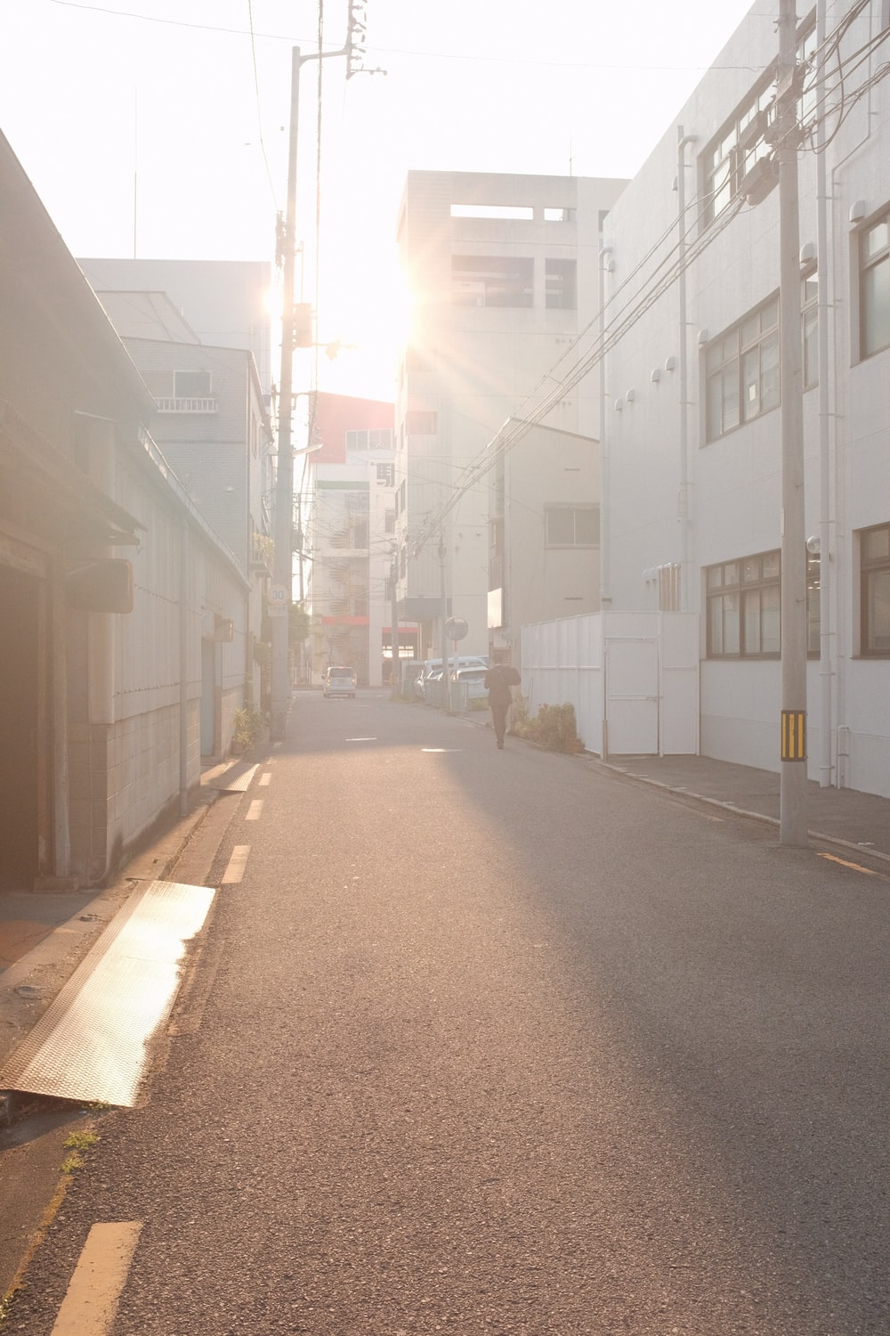 empty street between white concrete buildings during daytime