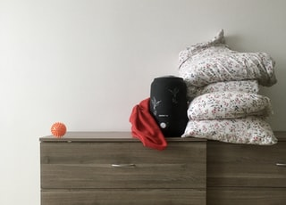 black and red backpack on brown wooden bed