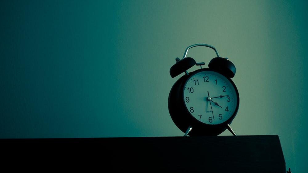 black and white analog alarm clock at 10 10