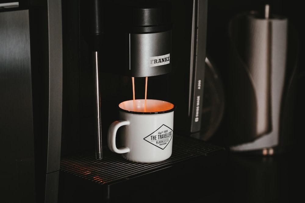 white ceramic mug on black and silver coffee maker
