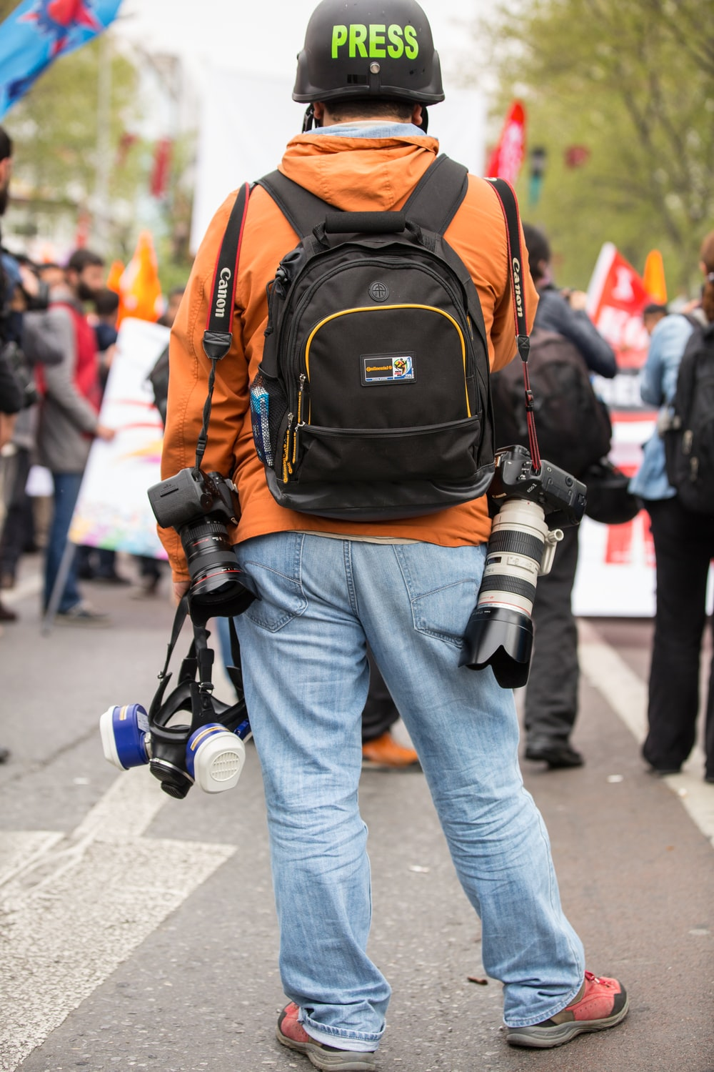 person in blue denim jeans and orange backpack walking on street during daytime