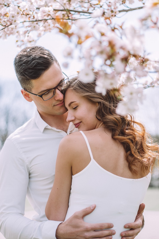 man in white dress shirt kissing woman in white tank top