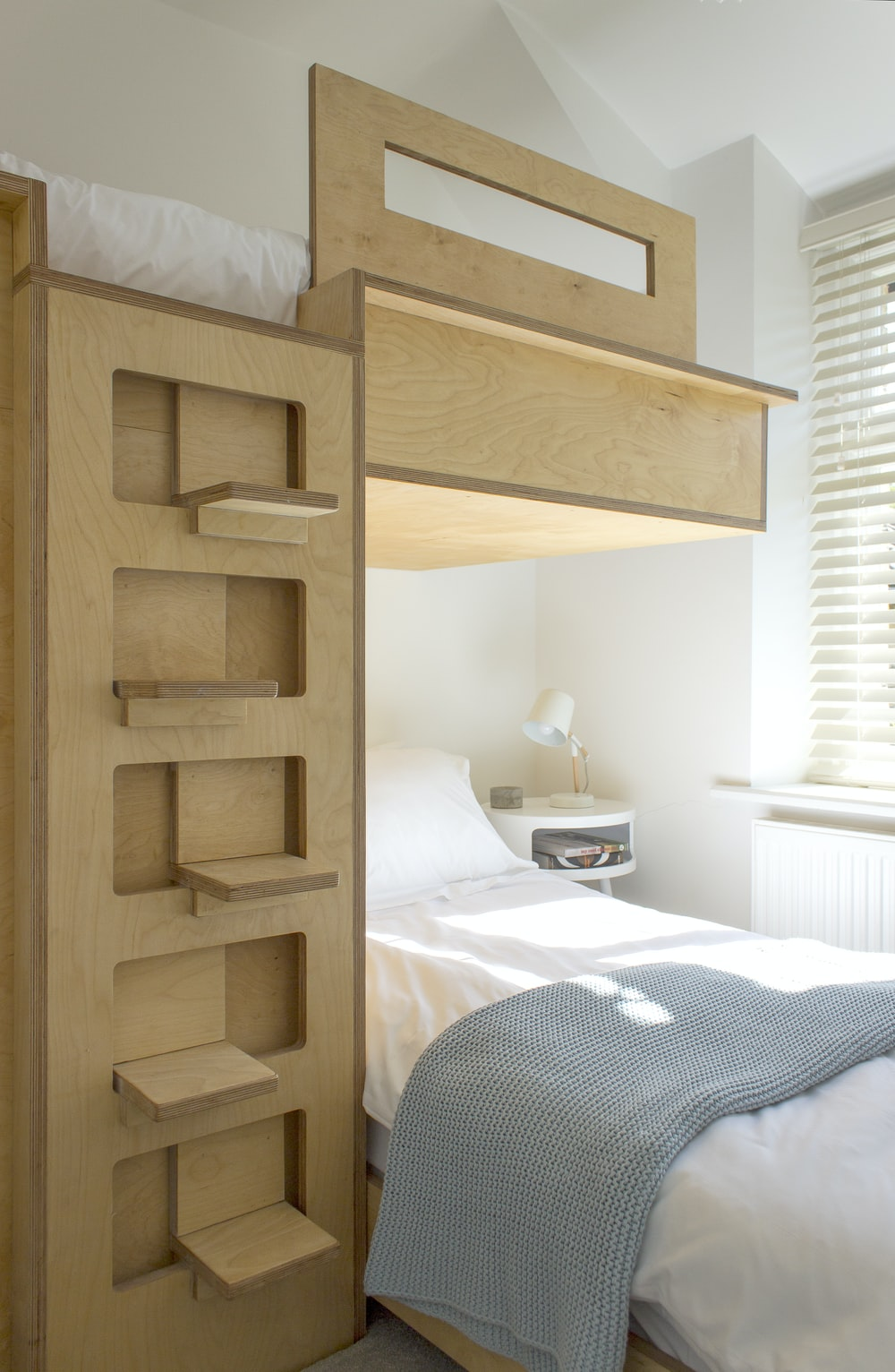 white bed linen near brown wooden bed frame