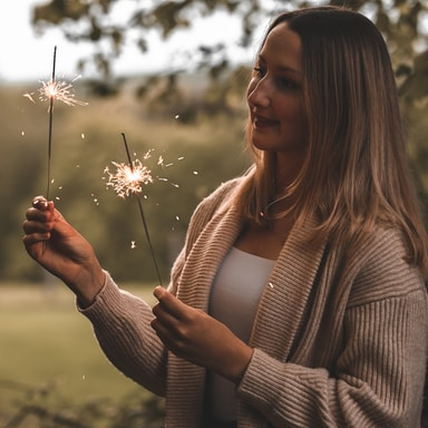 woman in white knit sweater holding white dandelion flower during daytime