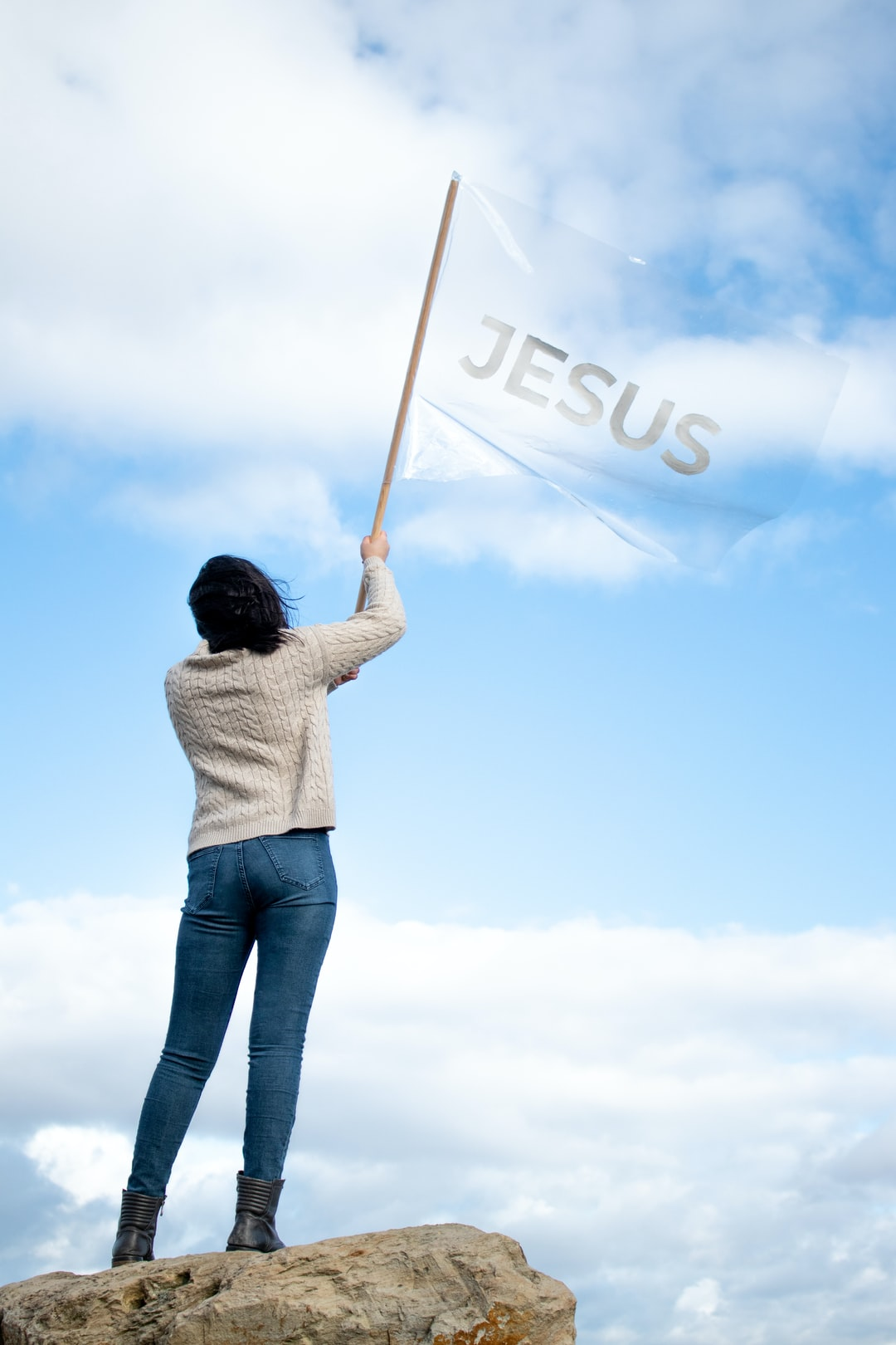 """Woman holding a flag with the word """"Jesus"""""""