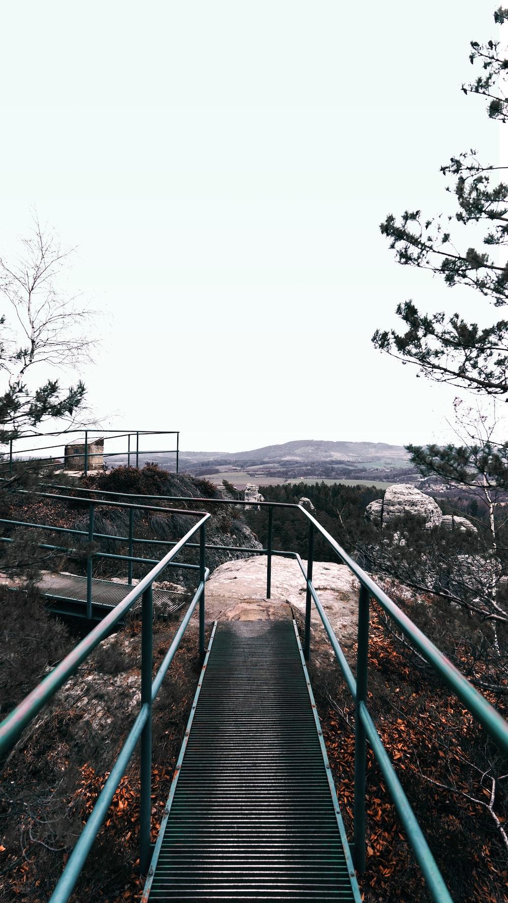 black metal railings on brown rocky mountain during daytime